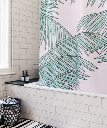 pink junique shower curtain with green palm tree print in bathroom