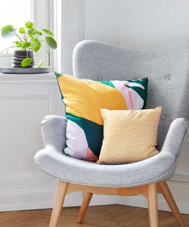 small yellow patterned cushion and large colourful juniqe cushion on chair