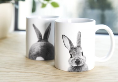 two white junique coffee mugs with black and white rabbit prints on table