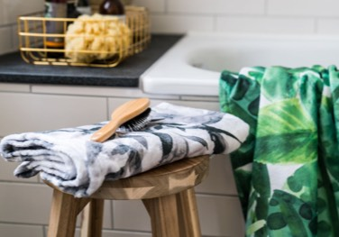grey patterned towel on stool and green leaf patterned bath towel