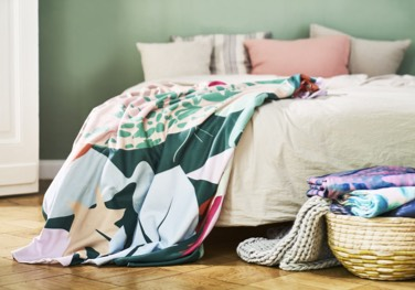 basket of printed fleece blankets in front of colouful juniqe fleece blanket on bed