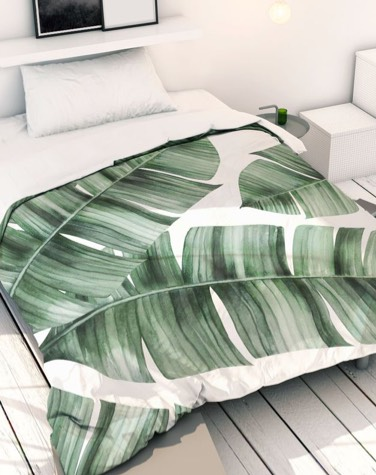 white bed linen printed with large green palm leaves on a bed in bedroom