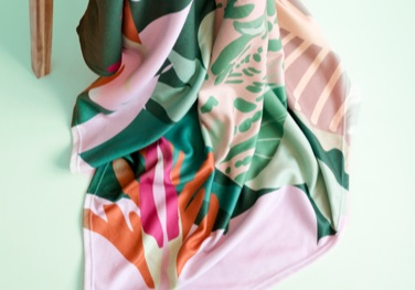 Colourful fleece blanket on a mint green floor
