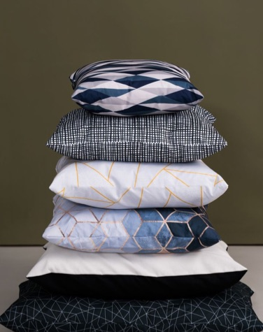 Pile of four cushions with abstract designs