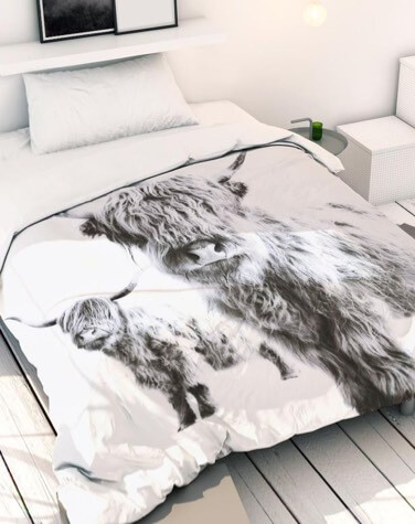 Bed with a duvet cover featuring a photo of a yak