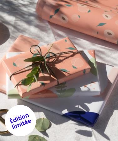 Cadeaux emballés avec papier cadeau pêche juniqe journelles sur table ensoleillée