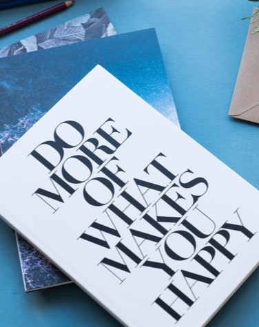 Notebook from JUNIQE printed with do more of what makes you happy design