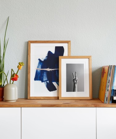 blue abstract poster and framed photograph of hand on sideboard