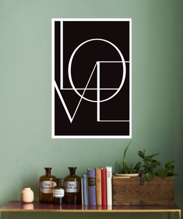 Black and white love poster above a table on a wall