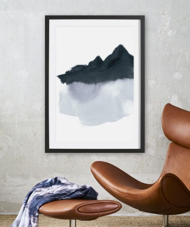 Painting of a mountain in a wooden frame hung above a chair
