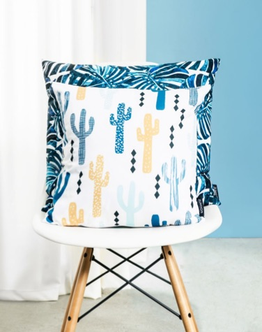 Cushions featuring monsteras and cacti stacked on chair