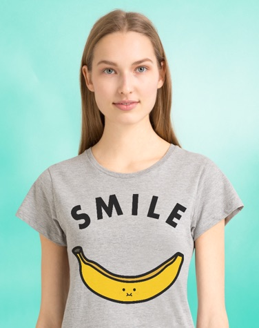 Woman in front of green background wearing SMILE banana t-shirt from juniqe