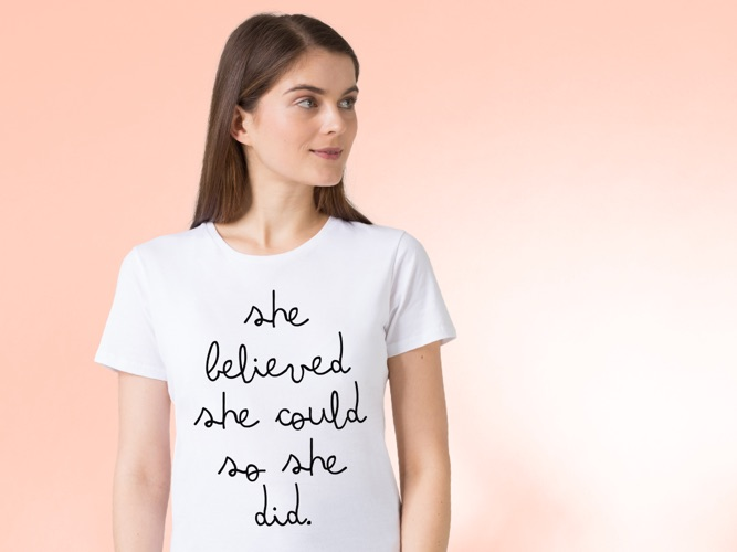 Model wearing white t-shirt with JUNIQE typography 'She believed she could so she did'