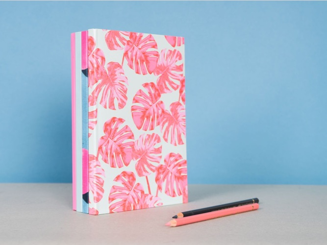 Stack of pastel notebooks with JUNIQE monstera designs