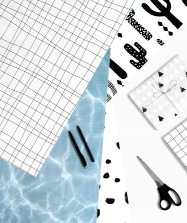 3 feuilles de papier cadeau design posées près de ciseaux