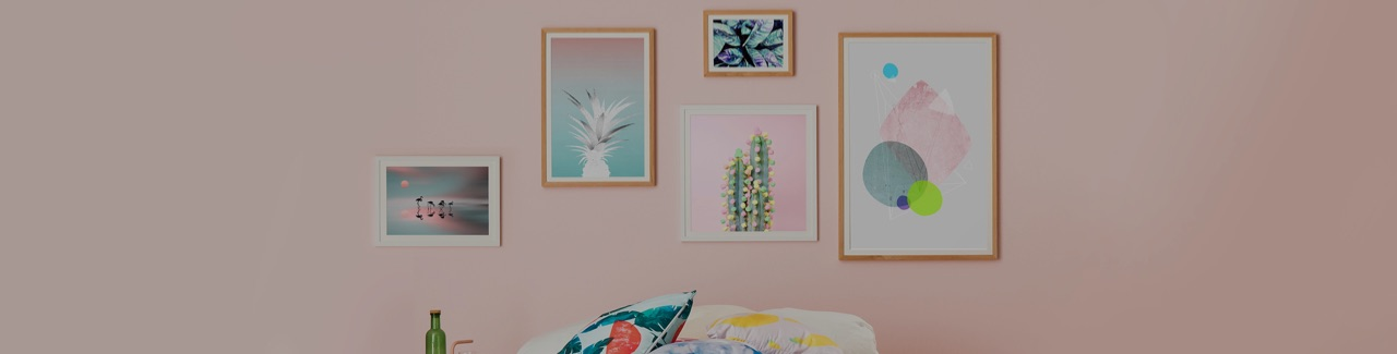 Wall with wood framed art prints in pastel colours