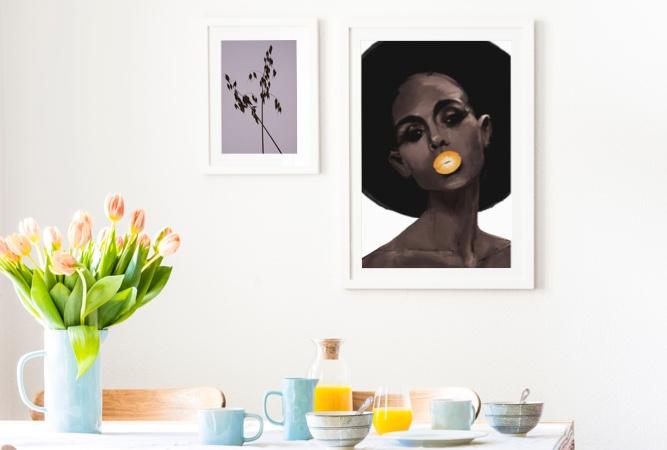 Gerahmte Prints an einer Wand hinter einem Frühstückstisch