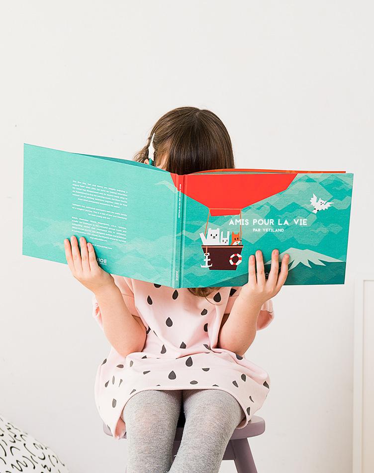 Petite fille lisant le livre pour enfant Amis pour la vie de Yetiland