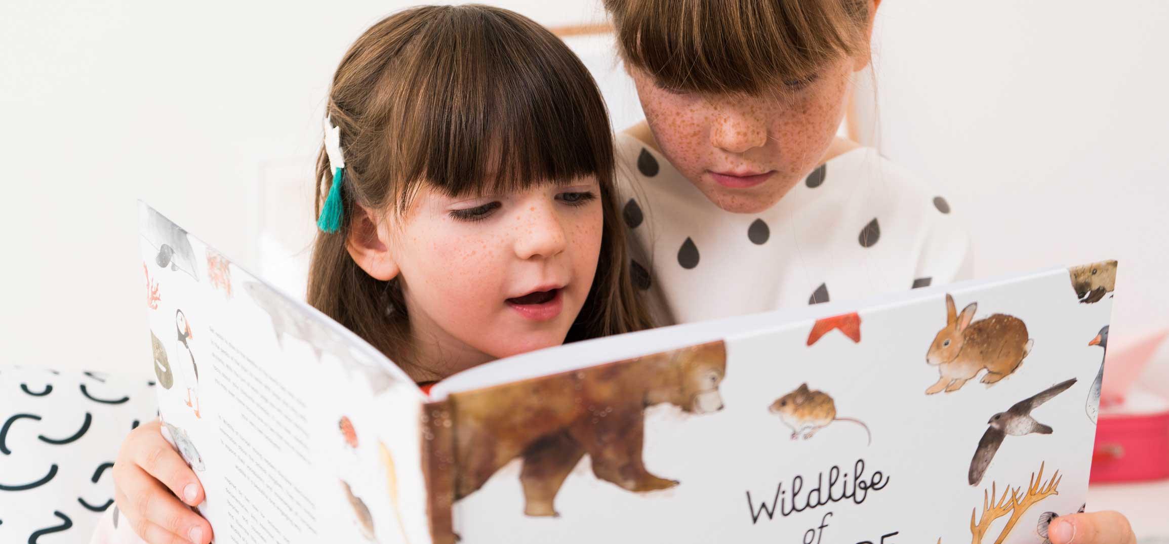 Zwei Mädchen lesen ein JUNIQE-Kinderbuch mit Tier-Illustrationen
