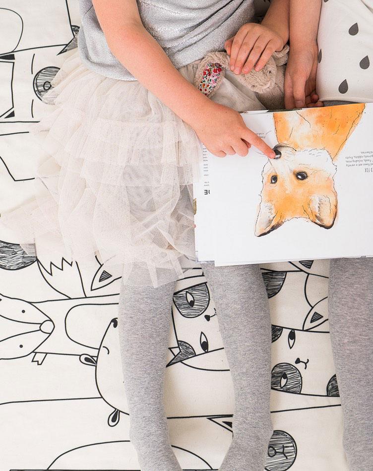 Auf dem Boden sitzende Mädchen, die ein Bilderbuch mit Tieren anschauen