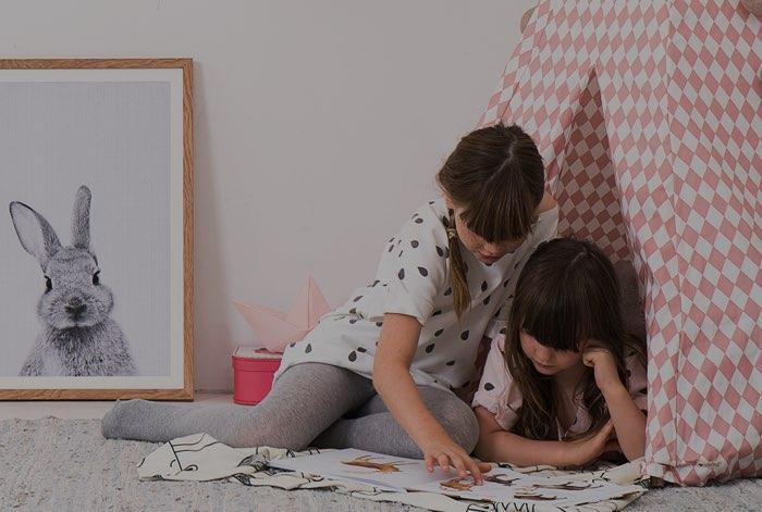 Zwei Mädchen lesen Kinderbücher in einer gemütlichen Leseecke