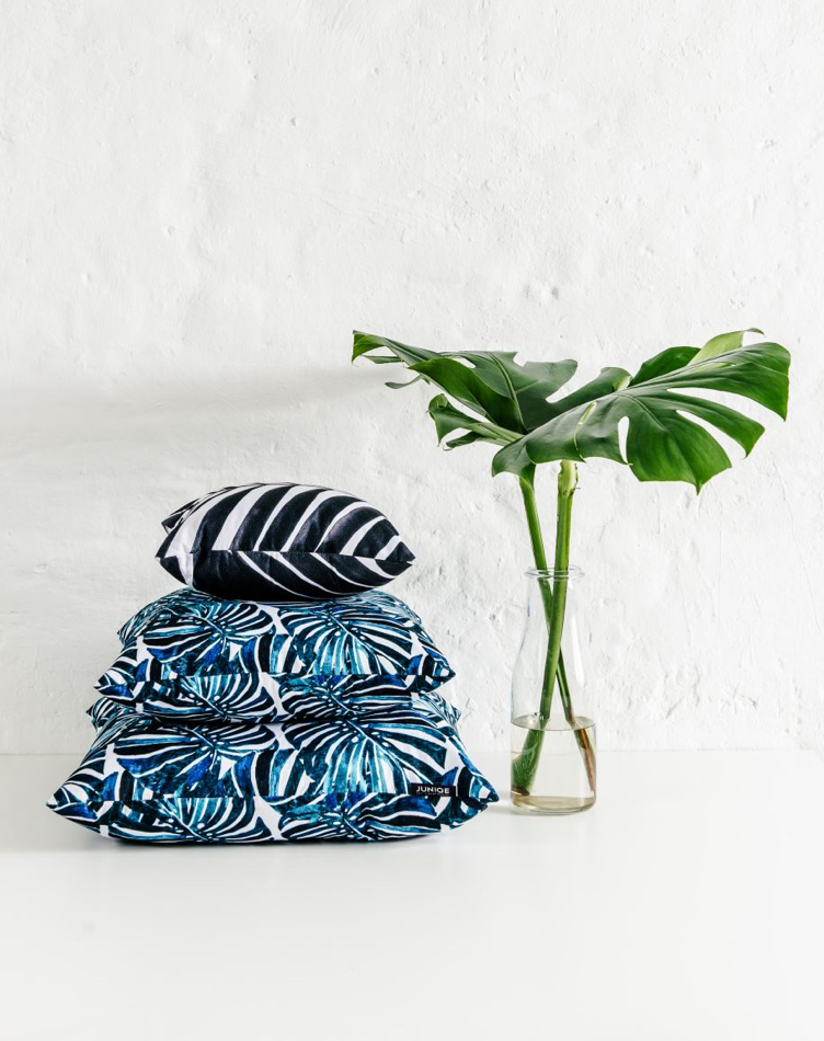 Pile of plant-themed pillows with leaves