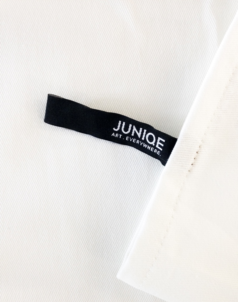The JUNIQE label can be used as a loop for hanging.